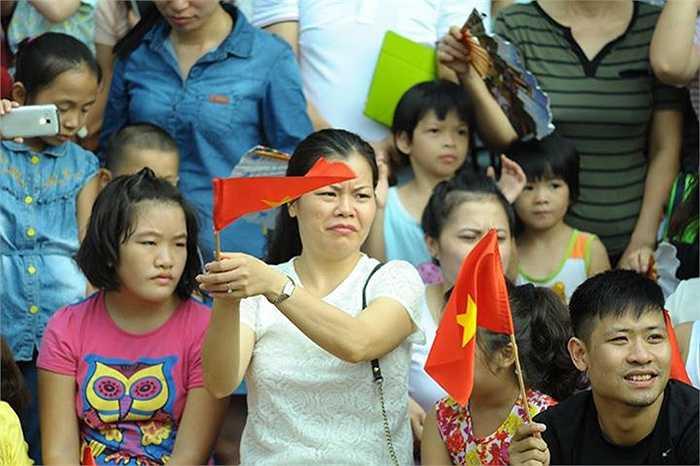 Một ảnh cũng được nhiều người chia sẻ là hình ảnh một người phụ nữ theo dõi đoàn diễu binh. Theo lời tác giả tấm hình, người phụ nữ này liên tục vẫy cờ, vỗ tay và hô to 'hoan hô' mỗi khi đoàn diễu binh đi qua, trái ngược hẳn với hình ảnh những người xung quanh chỉ giơ điện thoại lên để quay đoàn đi qua. Ảnh: Miu Linh