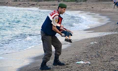 Nhân viên cứu hộ bế thi thể cậu bé lên bờ