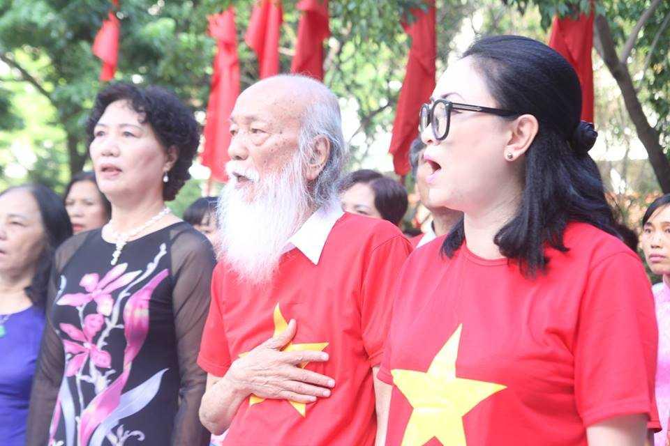 Thầy Văn Như Cương cũng mặc áo cờ đỏ sao vàng đưa tay lên đặt lên ngực, hát vang bài Quốc ca trong ngày khai giảng năm học mới
