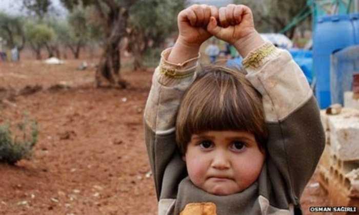 Phóng viên Osman Sagirli khi vừa giơ máy ảnh lên thì cô bé Adi Hudea vội vã giơ tay đầu hàng và mếu. Cử chỉ tưởng chừng như đơn giản nhưng thực sự khiến người ta phải một lần nữa thức tỉnh vì hoàn cảnh đáng thương của người dân trong vùng nội chiến Syria