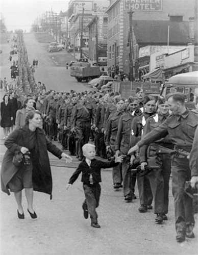 Hình ảnh mang tên 'Bố ơi Chờ con với' được chụp năm 1940 trước khi người bố ra trận chiến đấu trong Thế chiến II. Trước tương lai bất định và khoảnh khắc chia ly vì chiến tranh, nhiều người không thể cầm được nước mắt