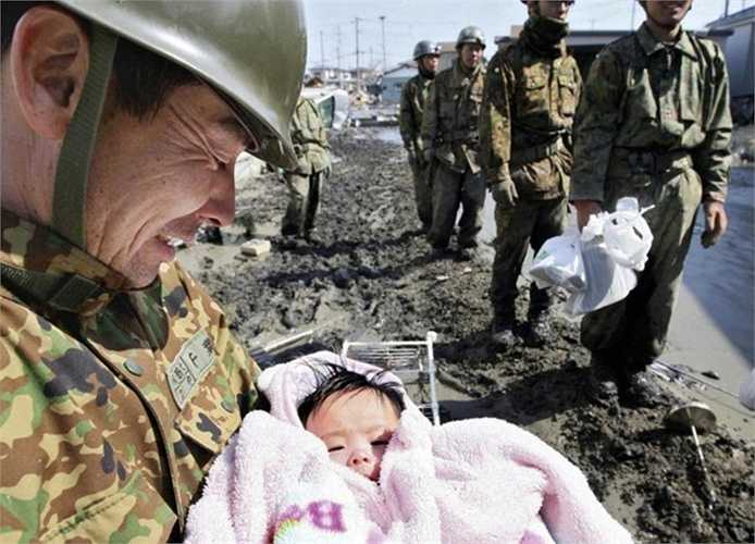 Bức ảnh chụp một nạn nhân 4 tháng tuổi được cứu thoát khỏi trận sóng thần năm 2011 tại Nhật Bản. Điều đáng nói là bé gái này đã sống sót một cách kỳ diệu trong đống đổ nát trước khi được các nhân viên cứu hộ giải thoát
