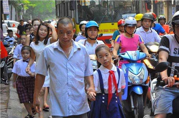 Phụ huynh cùng con gái đi bộ len lỏi giữa dòng phương tiện trước con đường dẫn vào trường Hoàng Hoa Thám.