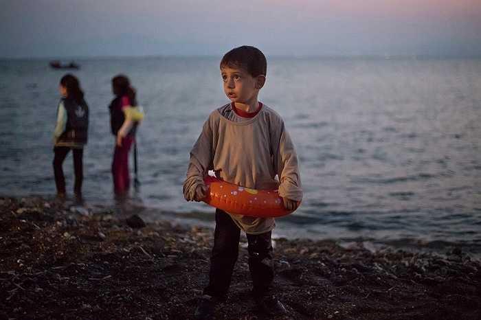Một bé trai Syria đứng trên bờ biển ở đảo Kos, Hy Lạp. Em đang tham gia hành trình di cư đầy nguy hiểm cùng gia đình
