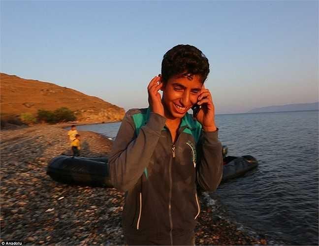 Một cậu bé tươi cười gọi điện báo với họ hàng là đã đến nơi an toàn