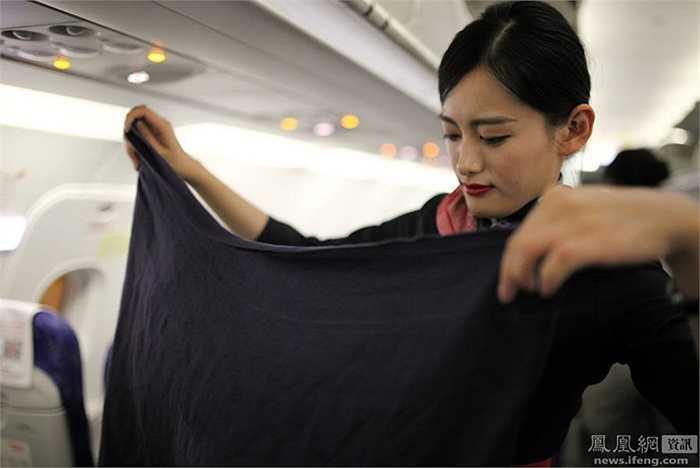 Cô Wang cẩn thận xếp lại chăn của khách sau chuyến bay. Nghề tiếp viên yếu tố ngoại hình là chưa đủ mà còn sự cần mẫn, chăm chỉ và tỉ mỉ