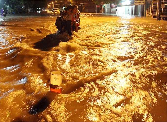 Nước chảy xiết khiến người phụ nữ này không thể đi, phải đeo bám vào dải phân cách đã bị nhấn chìm.