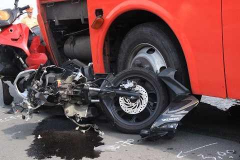 Xe máy bị cuốn vào gầm nát bươm