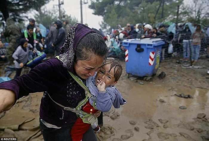 Người phụ nữ ôm con lội trong bùn lầy