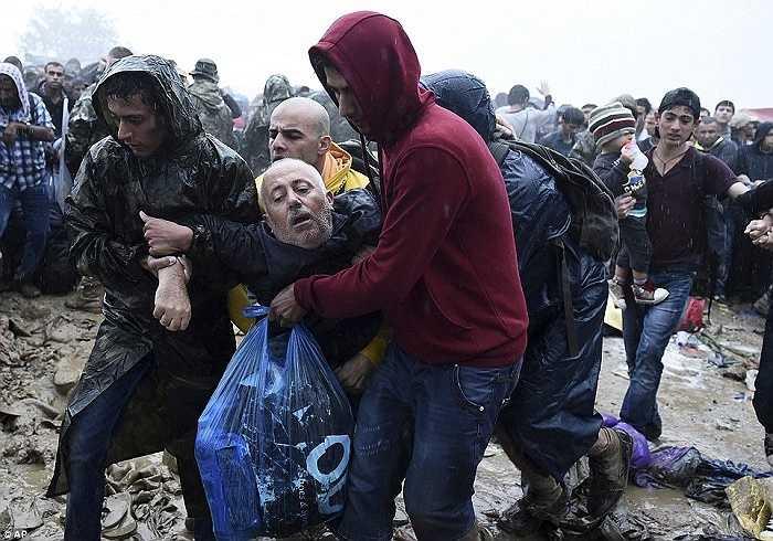 Người đàn ông kiệt sức sau nhiều giờ đồng hồ đứng dưới mưa lạnh. Một khi bạo lực, bất ổn và đói nghèo vẫn diễn ra thì vẫn còn người di cư muốn tìm đến 'miền đất hứa'