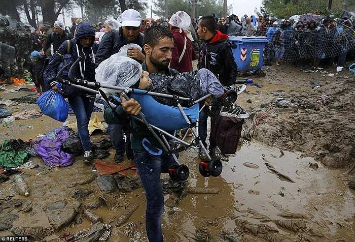 Một ông bố ôm con mình trên chiếc xe đẩy vượt biên