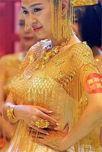 Người mẫu trong mẫu áo cưới làm từ vàng với các sợi vàng tạo nên nét uyển chuyể, khăn đội đầu cách điệu bằng chiếc mũ với nhiều sợi vàng tạo nên sự độc đáo