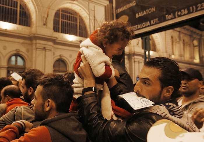 Một người di cư bế con chen chúc giữa đám đông ở nhà ga Keleti, Budapest, Hungary