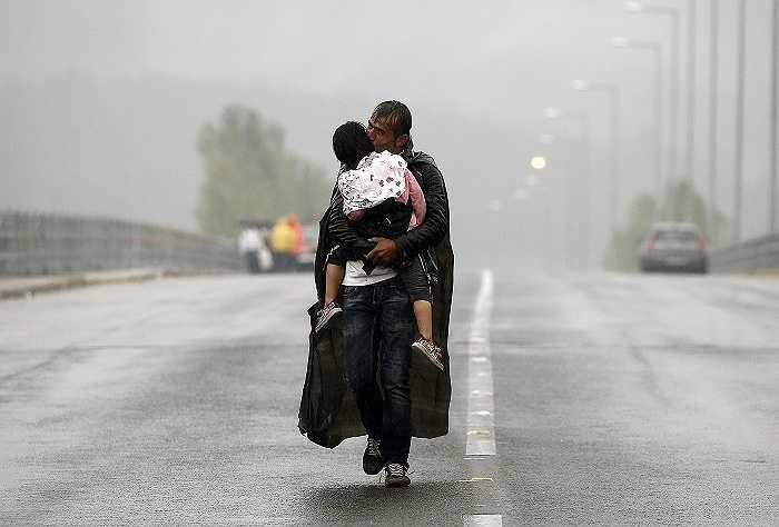 Một người đàn ông di cư bế cậu con trai nhỏ trên tay đi dưới trời mưa