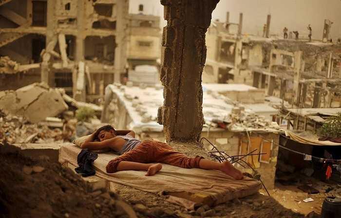 Cậu bé Palestine ngủ trên tấm nệm cũ nát bên trong ngôi nhà bị tàn phá trong trận chiến kéo dài 50 ngày hồi năm 2014