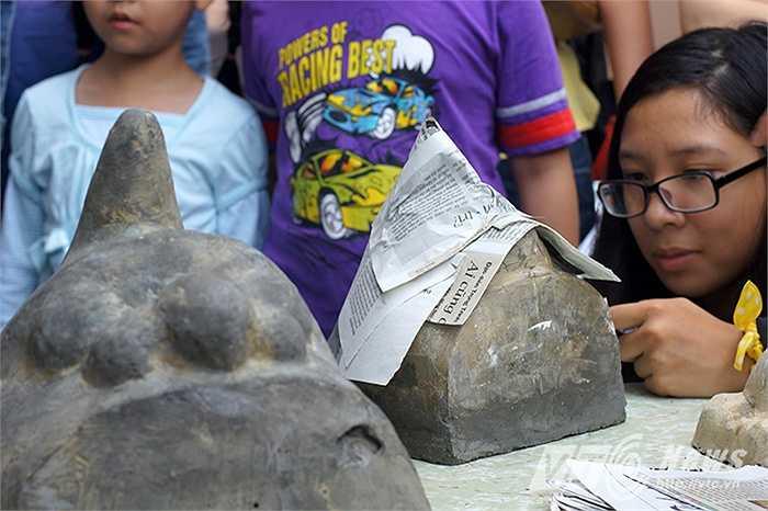 Một em nhỏ chăm chú học cách làm đầu Lân sư trên chiếc khuôn lồi.