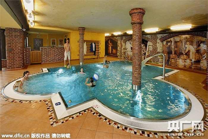 Bể bơi trong nhà được thiết kế rất ấn tượng, hình dạng độc đáo và lát đá sang trọng