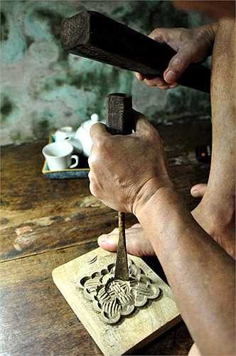 Trên tấm phản kê ở góc nhà, người đàn ông tuổi lục tuần vẫn đang cặm cụi đục, đẽo, hoàn thiện nốt chiếc khuôn bánh nước hình hoa sen.