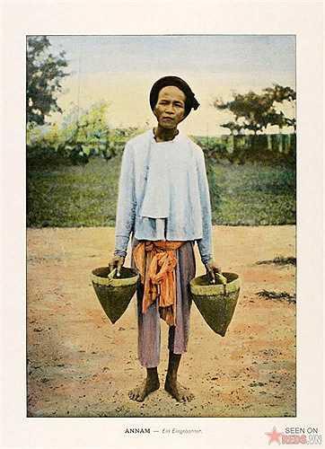 Người nông dân cầm đôi gầu dùng để tát nước.