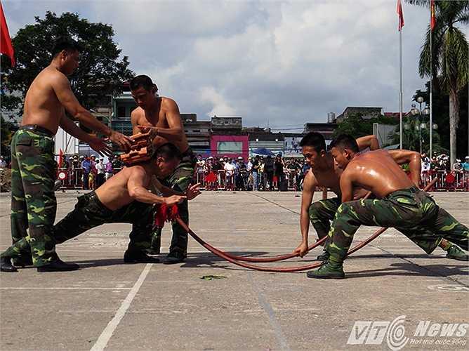 Màn biểu diễn đầu giáo nhọn cắm vào yết hầu, dùng khí công đẩy cong cán giáo, kết hợp chịu lực đập ngói trên lưng do đồng chí Nguyễn Mạnh Trường - Học viện Biên phòng thực hiện.