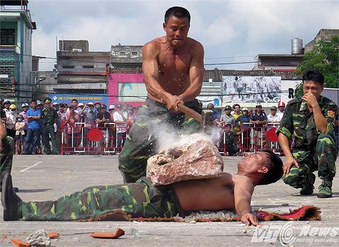 Màn biểu diễn nằm trên thuỷ tinh dùng búa tạ đập đá trên bụng do đồng chí Đinh Ngọc Hòa - Học viện Biên phòng thực hiện.