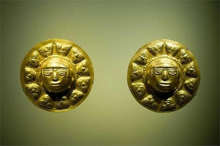 Đôi hoa tai bằng vàng, với một khuôn mặt người ở giữa và nhiều khuôn mặt nhỏ hơn xung quanh.