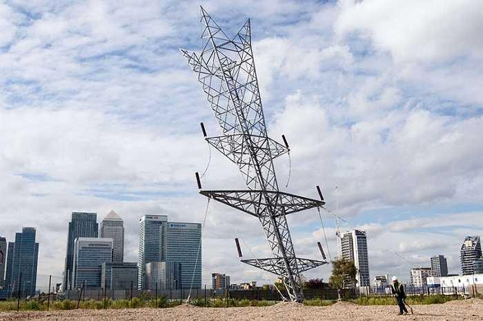 Một công nhân đi dưới tác phẩm điêu khắc của nghệ sĩ người Anh Alex Chinneck với tên gọi 'viên đạn từ sao băng', trên bán đảo Greenwich, London, Anh