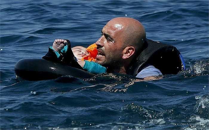 Một người tỵ nạn Syria bế một em bé trên phao cứu sinh và bơi vào bờ sau khi thuyền cao su chở họ bị xì hơi khi chỉ còn cách đảo Lesbos, Hy Lạp 100m