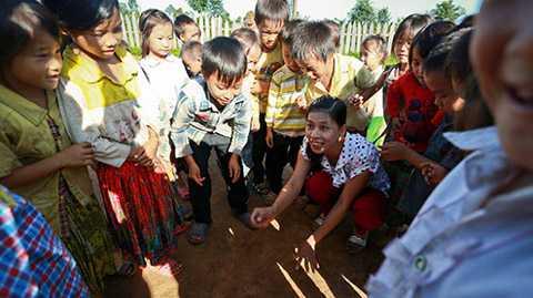 Cô giáo Lâm Thị Thu Thắm (lớp mầm non tại điểm trường thôn H'Mông) chơi đùa với các học sinh trên sân trường