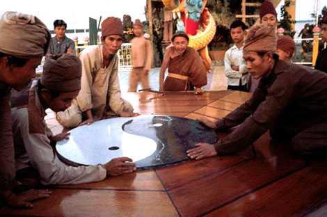 Ông đạo Dừa nhìn tín đồ đặt biểu tượng âm dương vào chiếc bàn hòa bình. Ảnh do nhà báo Tim Page chụp.