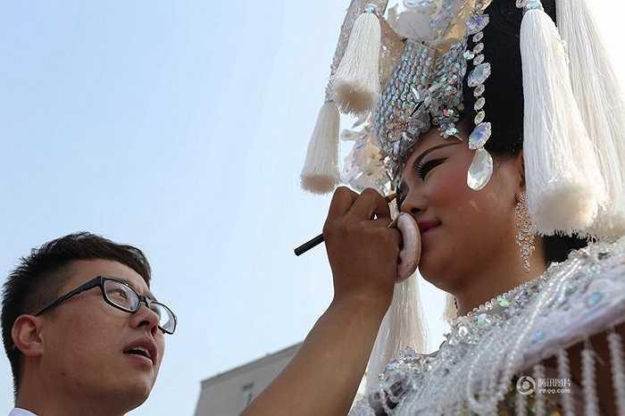 Nhà thiết kế Jiang Tao - tác giả của bộ áo cưới đang giúp người mẫu sửa sang lại chuẩn bị tạo dáng trước ống kính