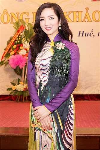 Cô khéo léo chọn chiếc áo dài màu tím Huế để đi dự sự kiện.