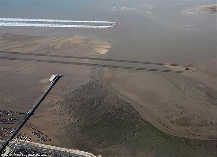 Bóng của đội bay và làn khói in xuống nền đất
