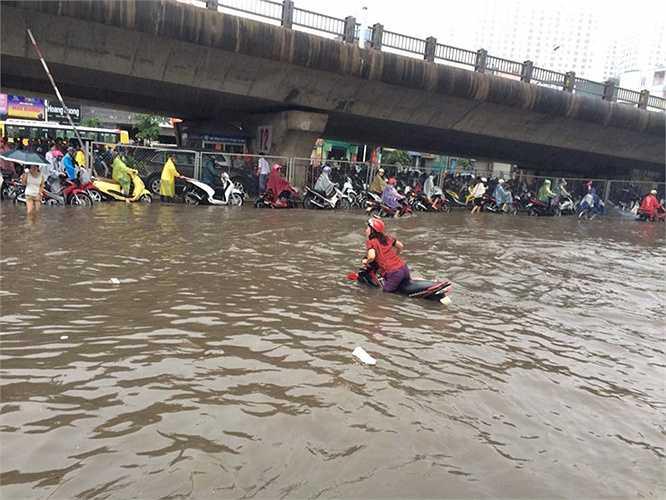 Người phụ nữ này rất khó khăn mới có thể dắt xe trong tình trạng nước ngập sâu như vậy. (Ảnh: N.T.Đ)