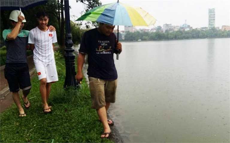 Hồ Đền Lừ, quận Hoàng Mai ngập nặng, nước tràn ra xung quanh. Thấy cua, lươn trườn lên bờ, nhiều người đã tranh thủ đội mưa đi bắt. (Nguồn: VnExpress)