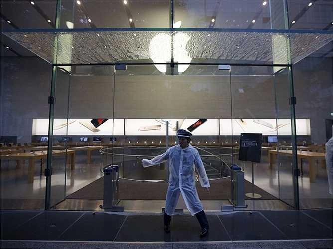 Một nhân viên cửa hàng Apple ở Tokyo, Nhật Bản phải làm việc sớm đế chuẩn bị đón khách vào mua iPhone đầu tiên