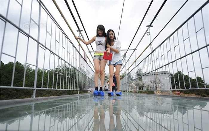 Hai cô gái chụp ảnh kỷ niệm trên cầu