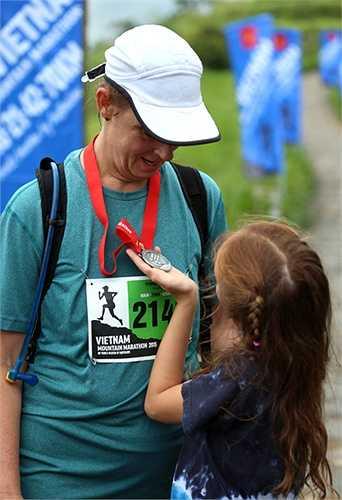 Cô con gái nhỏ nâng niu tấm huy chương của người mẹ vừa hoàn thành chặng đua 21km. (Ảnh: Quang Minh)