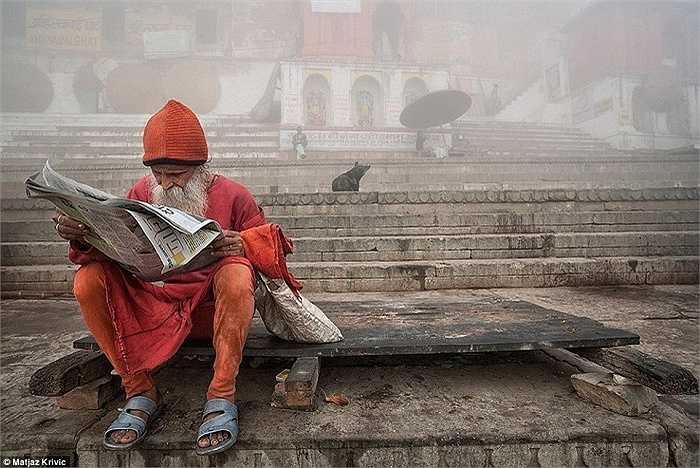Cụ già ngồi đọc báo ở một thị trấn yên bình vào buổi sáng sớm bên bờ sông Hằng