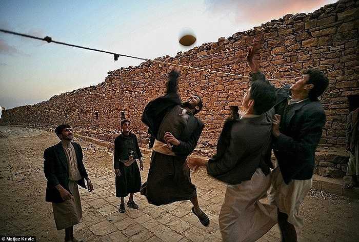 Những chàng trai trẻ chơi bóng chuyền trên đường phố ở thị trấn lịch sử Thula, Yemen