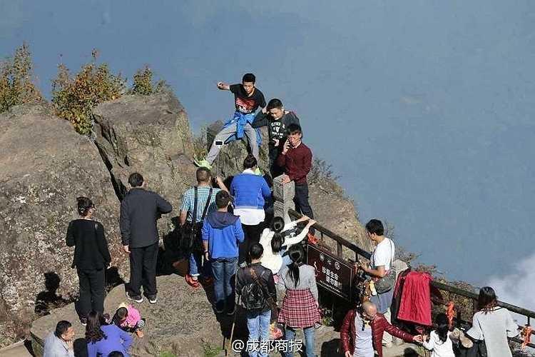 Du khách mạo hiểm bất chấp biển cảnh báo leo ra ngoài hàng rào để chụp ảnh.
