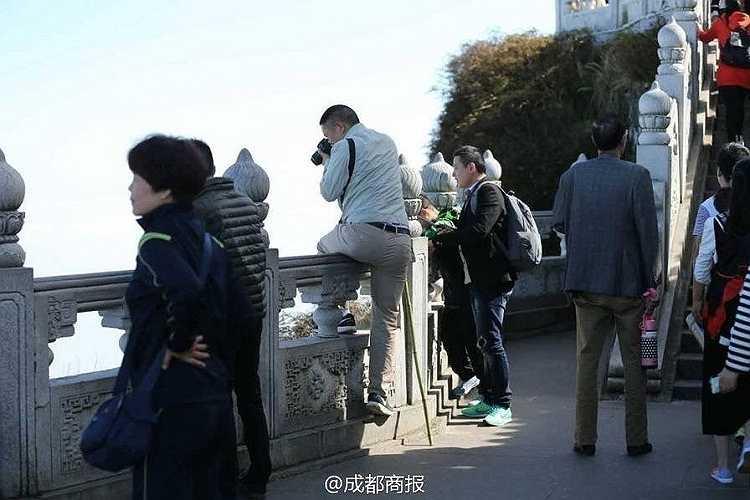 Một du khách vắt chân qua lan can để cố chụp một bức ảnh phong cảnh đẹp.