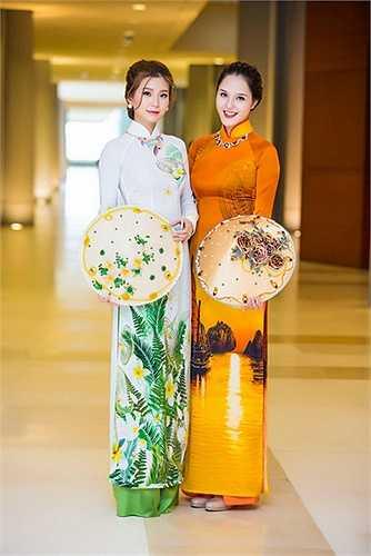 Hoàng Anh diện áo áo dài cam, in bức tranh về Vịnh Hạ Long, riêng Diễm Trang lại mặc áo dài trắng với hoạ tiết hoa lá