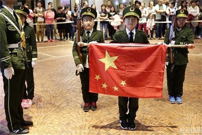 Bé học sinh bên quốc kỳ Trung Quốc