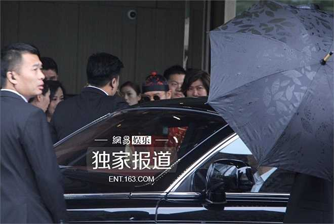 Thượng Hải đổ mưa vào sáng 8/10. Huỳnh Hiểu Minh (áo đỏ, kính đen, mũ nồi) giúp cô dâu vào xe hoa.