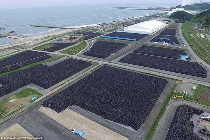 Những bao tải đất bị ô nhiễm phóng xạ được các nhân viên vệ sinh xếp gọn gàng trên mặt đất.
