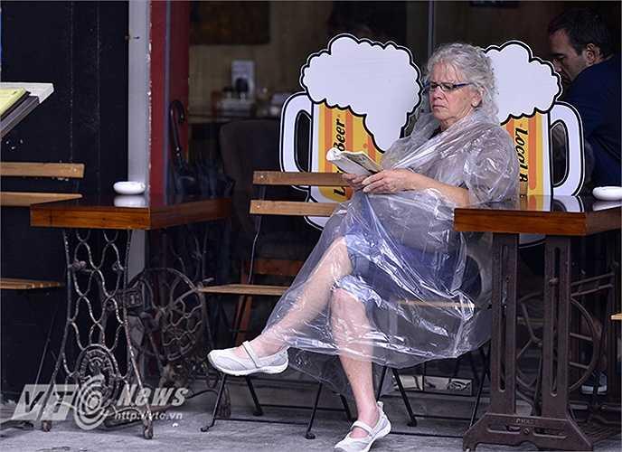 Một vị khách du lịch vừa khoác lên mình chiếc áo mưa mỏng vừa ngồi đọc sách bên phố Đinh Liệt (Hoàn Kiếm, Hà Nội)