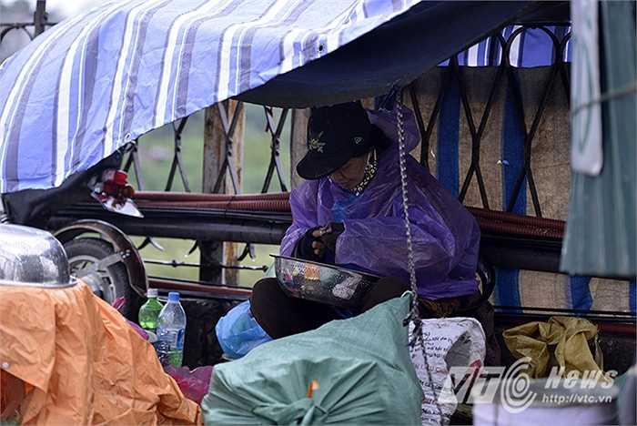 Cô Hiền (Long Biên, Hà Nội) phải dựng bạt và mặc áo mưa để che gió, cô cho biết: 'Ngày mưa gió rét mướt nên cũng chẳng có mấy khách mua hàng.'