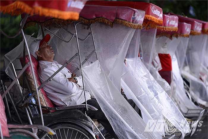 Những người đạp xích lô che áo mưa chờ khách trên đường Trần Quang Khải.