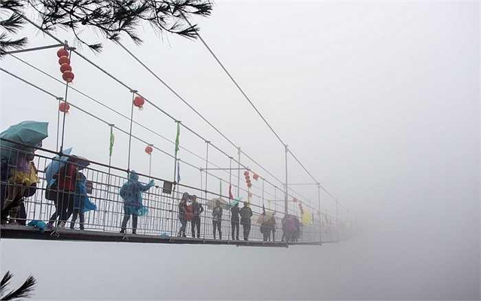 Khách du lịch đi qua cây cầu treo bằng kính trong màn sương mù dày đặc ở vùng núi Shinuizhai, tỉnh Hồ Nam, Trung Quốc
